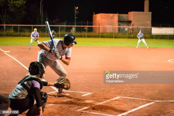 softball hitter and catcher waiting for ball - softball stock pictures, royalty-free photos & images