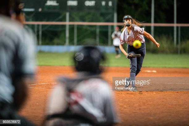 softball pitcher looking at the ball mid air - softball stock pictures, royalty-free photos & images