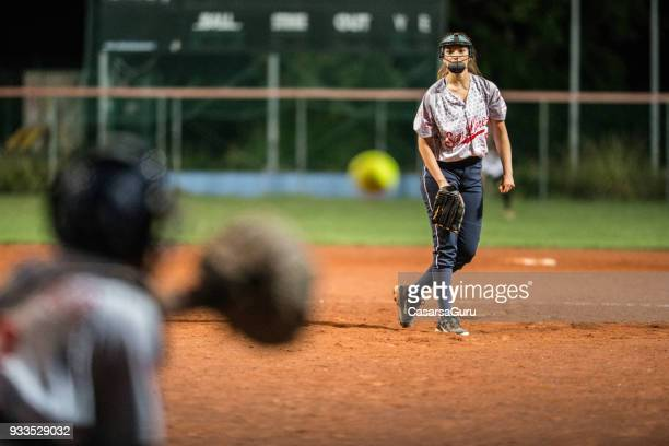 softball pitcher looking at the ball mid air - baseball pitcher stock pictures, royalty-free photos & images