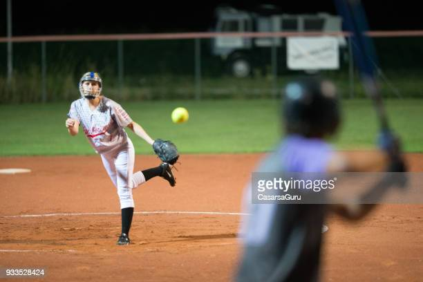 softball pitcher throwing the ball to batter - baseball pitcher stock pictures, royalty-free photos & images
