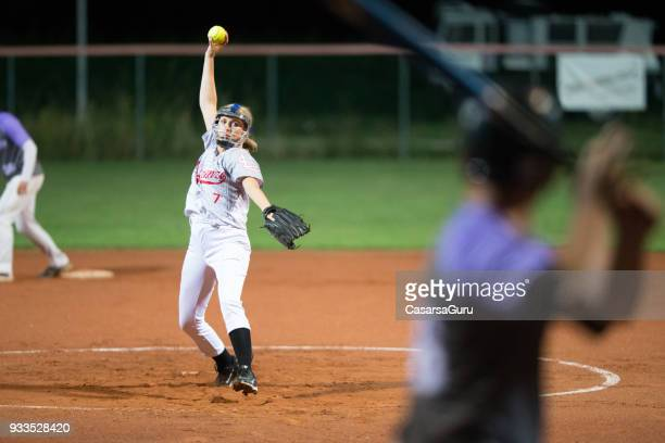 softball player in mid throw - softball stock pictures, royalty-free photos & images