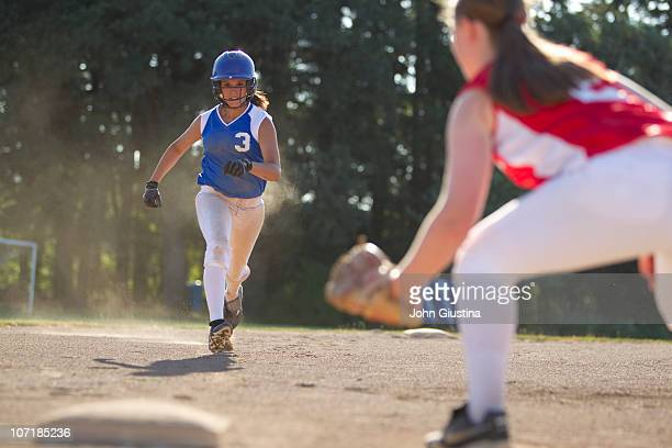 Softball player runs to third base.