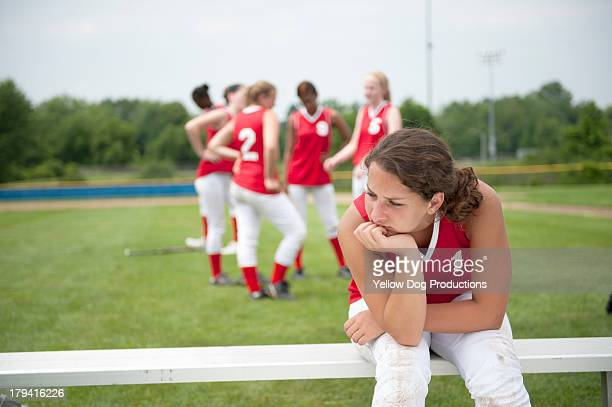 softball player sitting on bench with head down - softball sport stock pictures, royalty-free photos & images