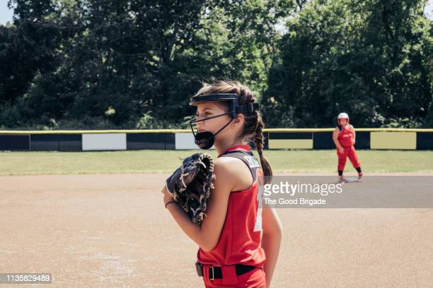 softball player standing on pitcher's mound - girl mound stock pictures, royalty-free photos & images
