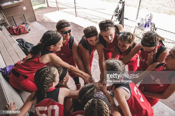 softball players huddle in dugout - youth league foto e immagini stock