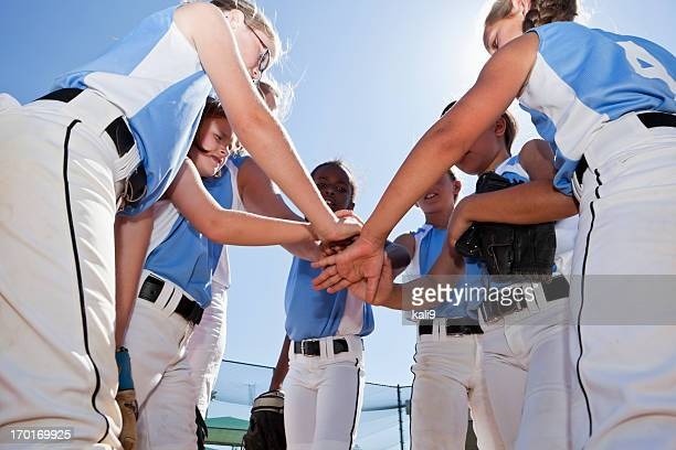 softball players with coach in huddle doing team cheer - softball stock pictures, royalty-free photos & images
