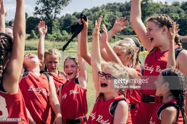 softball team cheering on field - softball sport stock pictures, royalty-free photos & images