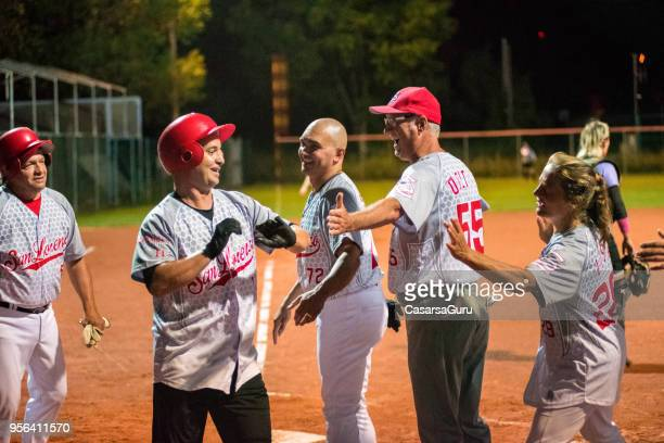 softball team congratulating to a player - softball stock pictures, royalty-free photos & images