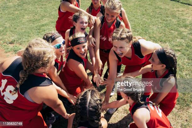softball team huddling on field - softball sport stock pictures, royalty-free photos & images