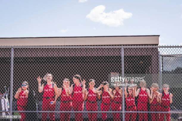 softball team standing by fence in dugout - softball sport stock pictures, royalty-free photos & images