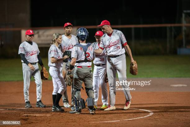 softball team talking strategy - softball stock pictures, royalty-free photos & images