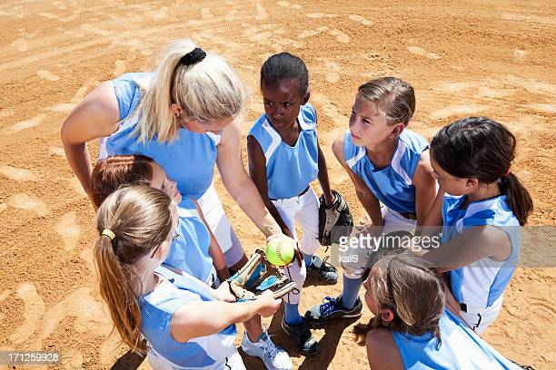 softball team with coach in huddle - softball sport stock pictures, royalty-free photos & images
