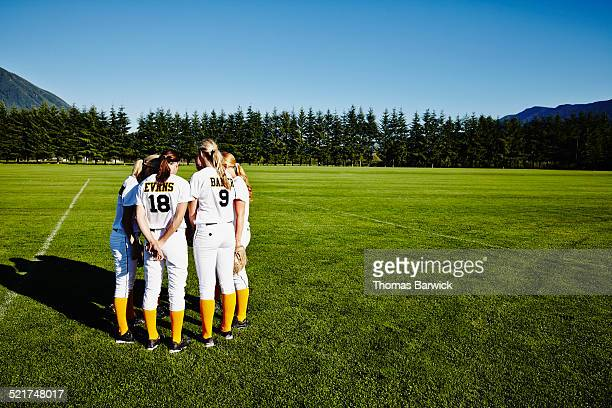 Softball teammates huddle in field before game