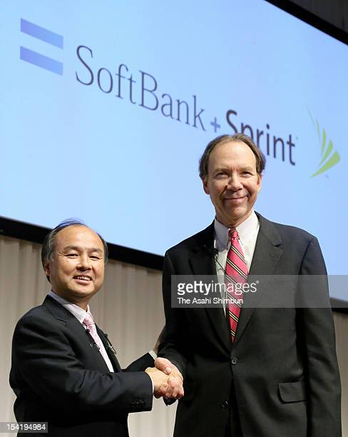 Softbank Corp chairman and CEO Masayoshi Son and Sprint Nextel Corp President and CEO Dan Hesse shake hands during a press conference on October 15...