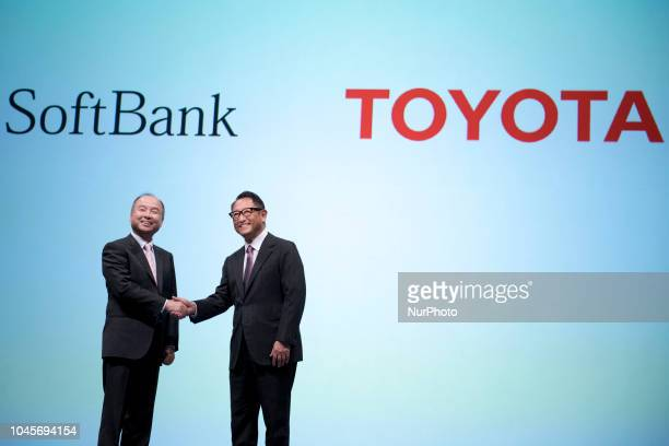 SoftBank Corp. Chief Executive Officer Masayoshi Son and Toyota Motor Corp President Akio Toyoda shake hands during a joint announcement of their new...