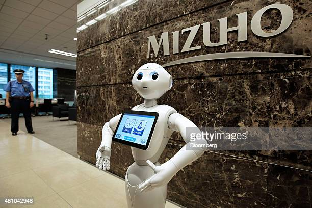 SoftBank Corp's humanoid robot Pepper stands at a Mizuho Bank Ltd branch in Tokyo Japan on Friday July 17 2015 Mizuho introduced Pepper robot to its...