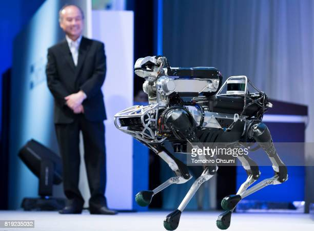 SoftBank Group Corp Chief Executive Officer Masayoshi Son looks at a Boston Dynamics Inc SpotMini robot during a demonstration at the SoftBank World...