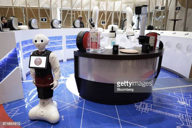 A SoftBank Group Corp Pepper humanoid robot left and a Kawasaki Heavy Industries Ltd twoarmedduArorobot rear stand next to a counter serving...
