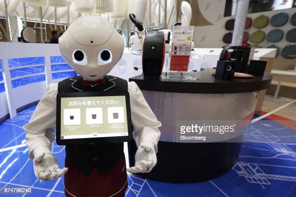 A SoftBank Group Corp Pepper humanoid robot stands during a media preview of the humanless cafe at the Nestle SA's Nescafe coffee shop in the...
