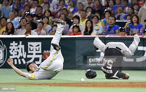SoftBank Hawks first baseman Seiichi Uchikawa gets injured in a collision with Alfredo Despaigne of the Lotte Marines in the eighth inning of a...