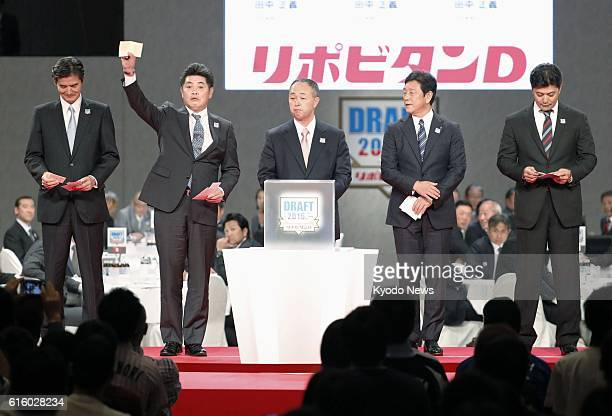 SoftBank Hawks manager Kimiyasu Kudo holds up the winning lot in a fiveway lottery for the exclusive right to negotiate a contract with Soka...