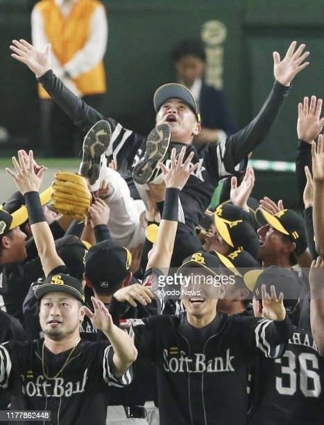 SoftBank Hawks manager Kimiyasu Kudo is tossed into the air after they completed a four-game sweep of the Yomiuri Giants to win their third...