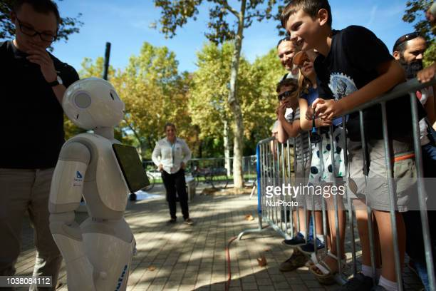 A SoftBank robot exchanges with children A robots race took place in Toulouse Machines are either cars or walking robots They were supposed to run a...