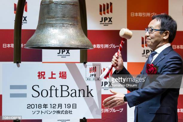 SoftBank Corp Chief Executive Officer Ken Miyauchi hits a bell during a ceremony for the company's listing at the Tokyo Stock Exchange on December 19...