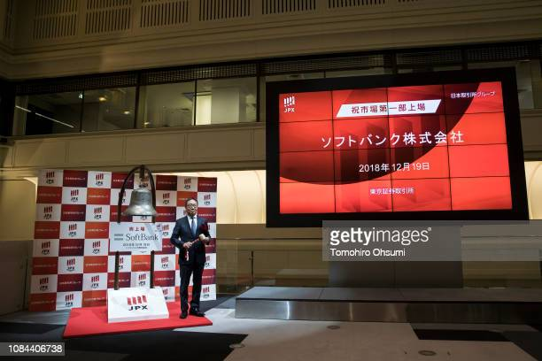 SoftBankCorp. Chief Executive Officer Ken Miyauchi poses before hitting a bell during a ceremony for the company's listing at the Tokyo Stock...