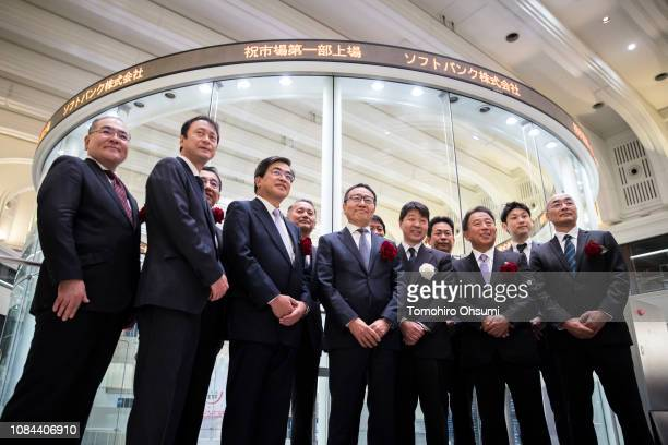SoftBankCorp. Chief Executive Officer Ken Miyauchi poses for a group photograph during a ceremony for the company's listing at the Tokyo Stock...