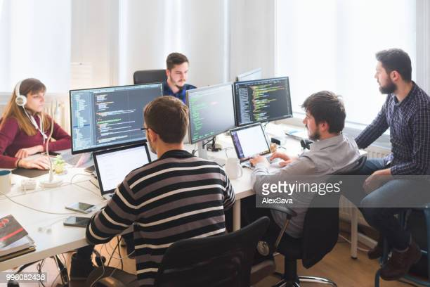 software developing team working in the office - coding stock pictures, royalty-free photos & images
