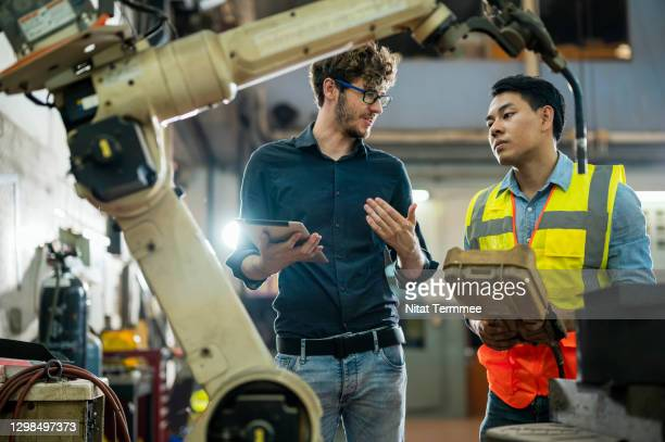 software engineer explaining to controlling robotic welding process to welder in factory. - robot stock pictures, royalty-free photos & images