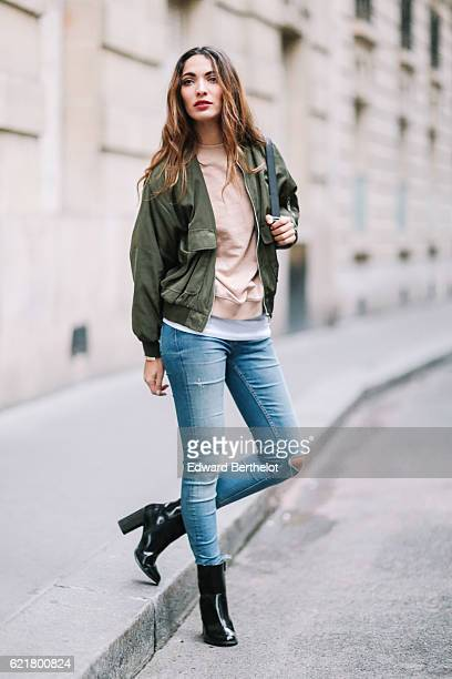 Sofya Benzakour is wearing a Boohoo green bomber jacket a Nakd Fashion pink pull over Zara blue denim jeans pants New Look shoes and a multi color...