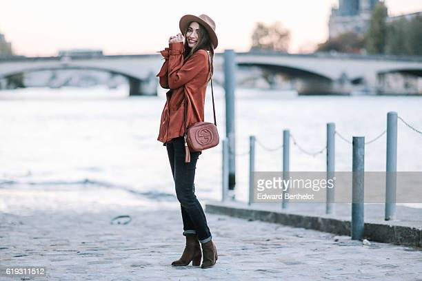 Sofya Benzakour is wearing a hat Reiko denim jeans a Nakd Fashion orange shirt Zara boots and a Gucci brown bag on October 30 2016 in Paris France
