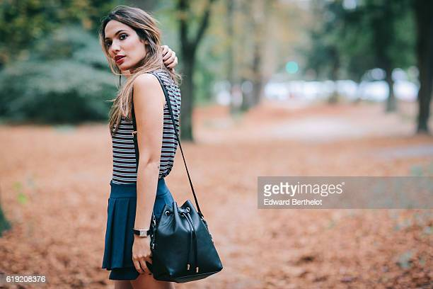 Sofya Benzakour is wearing a Pimkie full outfit made of a striped sleeveless shirt a purple coat a blue skirt a black bag and black shoes on October...