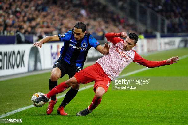 Sofyan Amrabat of Club Brugge and Zlatko Junuzovic of Salzburg fight for the ball during the UEFA Europa League Round of 32 match between FC Salzburg...