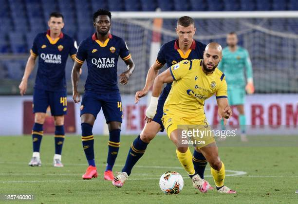 Sofyan Amrabat of Hellas Verona and Edin Dzeko of AS Roma compete for the ball during the Serie A match between AS Roma and Hellas Verona at Stadio...