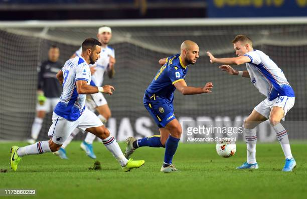 Sofyan Amrabat of Hellas Verona competes for the ball with Fabio Quagliarella and Jakub Jankto of UC Sampdoria during the Serie A match between...