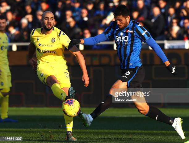 Sofyan Amrabat of Hellas Verona is challenged by Jose Luis Palomino of Atalanta BC during the Serie A match between Atalanta BC and Hellas Verona at...
