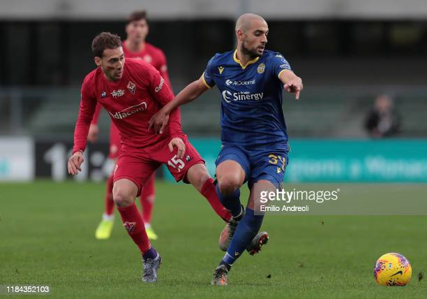 Sofyan Amrabat of Hellas Verona is challenged by Sebastian Cristoforo of ACF Fiorentina during the Serie A match between Hellas Verona and ACF...