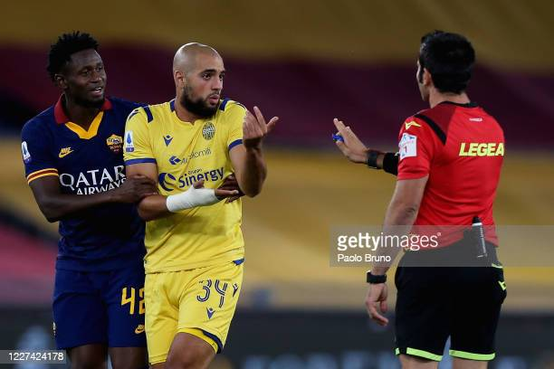 Sofyan Amrabat of Hellas Verona protests with the referee Fabio Maresca as Amadou Diawara of AS Roma reacts during the Serie A match between AS Roma...