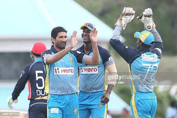 Sohail Tanvir and Darren Sammy celebrate the wicket of Ben Dunk with wicket keeper Andre Fletcher during a match between St Lucia Zouks and Antigua...