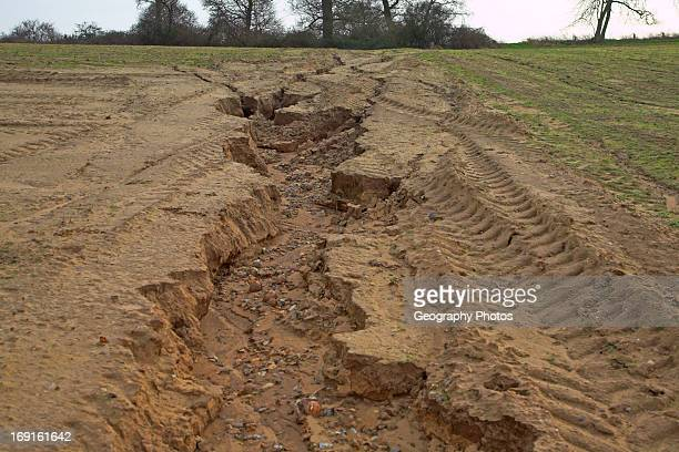 Soil erosion in sandy soil caused by run off in field ploughed downhill Butley Suffolk England