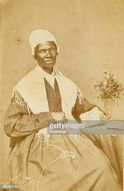 Sojourner Truth threequarter length portrait seated at table with knitting and book
