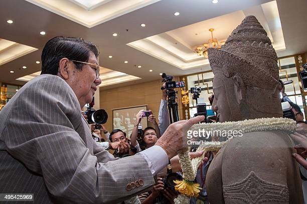 Sok An Deputy Prime Minister of Cambodia deposits a traditional Cambodian crown of flowers in front of the Balarama statue during a handover ceremony...
