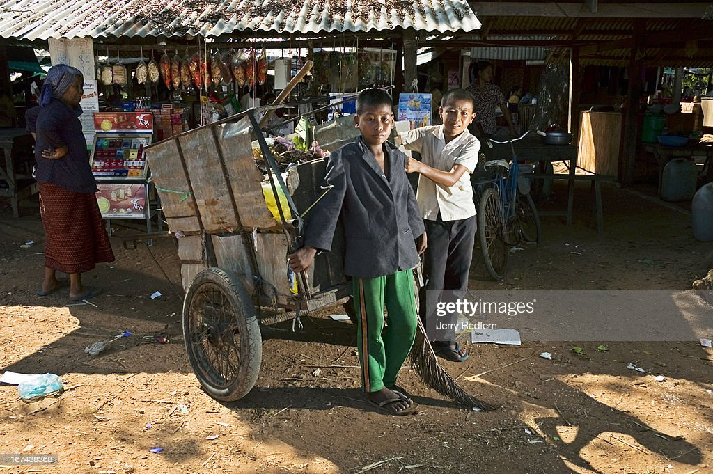 Sok Ketha, 13, (left) and Sok Buthy, 15, collect the garbage in a rural market. Working with their father every day after school, the three make 70,000 Riel (US $17.50) per month. The vast majority of Cambodian children work. Their labor is imperative for their survival and the survival of their families. In rural areas, kids are expected to work beside their parents on farms. In cities, they are sent out to sell flowers, drinks or shine shoes for extra money. Everywhere, as soon as they are able, children are expected to take care of their younger siblings and take up difficult family chores, work that is usually reserved for parents or servants in the developed world. In Cambodia, kids work everywhere, and form a significant, underreported part of the country's economy..