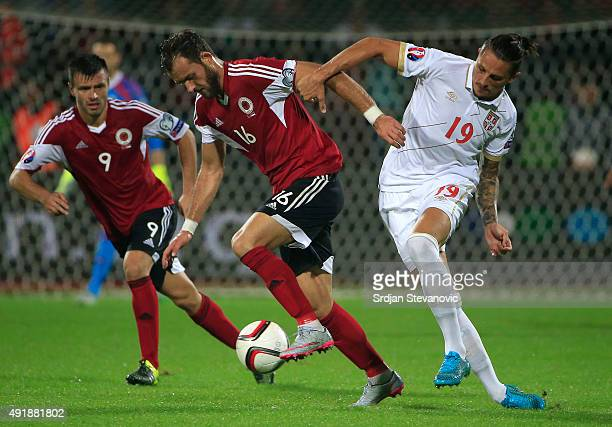 Sokol Cikalleshi of Albania is challenged by Ljubomir Fejsa of Serbia during the Euro 2016 qualifying football match between Albania and Serbia at...