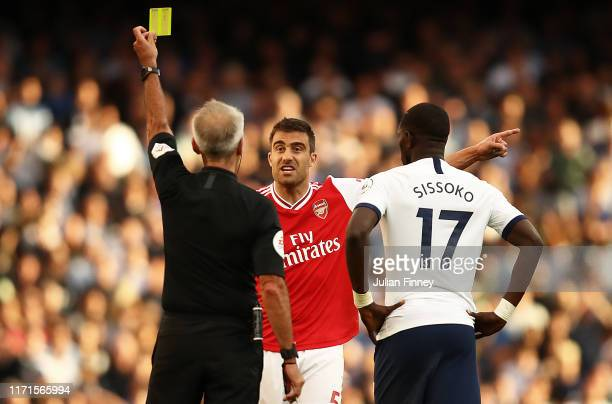 Sokratis of Arsenal is shown a yellow card by referee Martin Atkinson during the Premier League match between Arsenal FC and Tottenham Hotspur at...