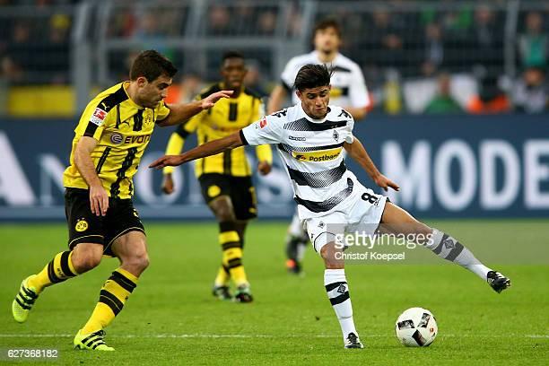 Sokratis of Dortmund challenges Mahmoud Dahoud of Moenchengladbach during the Bundesliga match between Borussia Dortmund and Borussia...