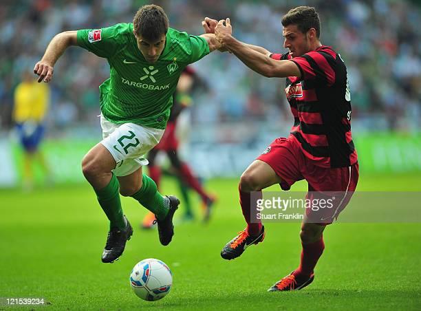 Sokratis of Werder is challenged by Daniel Caligiuri of Freiburg during the Bundesliga match between SV Werder Bremen and SC Freiburg at Weser...